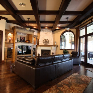Family room - large mediterranean open concept dark wood floor family room idea in Tampa with beige walls, a corner fireplace, a stone fireplace and a media wall