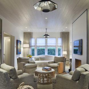 Exemple d'une salle de séjour bord de mer avec un mur blanc, un sol en bois foncé, aucune cheminée, un téléviseur fixé au mur et un sol beige.