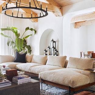 Idee per un grande soggiorno mediterraneo aperto con pareti marroni, pavimento in ardesia, camino classico, cornice del camino in cemento, TV a parete e pavimento marrone