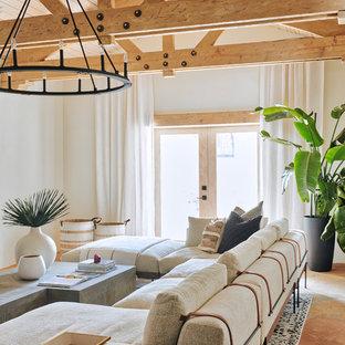 Aménagement d'une grande salle de séjour méditerranéenne ouverte avec un mur marron, un sol en ardoise, une cheminée standard, un manteau de cheminée en béton, un téléviseur fixé au mur et un sol marron.