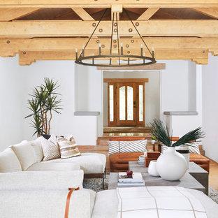 Esempio di un grande soggiorno mediterraneo aperto con pareti marroni, pavimento in ardesia, camino classico, cornice del camino in cemento, TV a parete e pavimento marrone