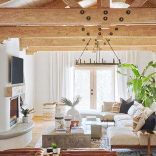 Foto di un grande soggiorno mediterraneo aperto con pareti marroni, pavimento in ardesia, camino classico, cornice del camino in cemento, TV a parete e pavimento marrone