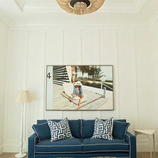 マイアミのビーチスタイルのおしゃれなファミリールーム (白い壁、淡色無垢フローリング、ベージュの床) の写真