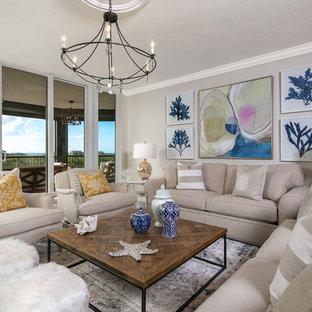 タンパの大きいビーチスタイルのおしゃれなオープンリビング (ベージュの壁、壁掛け型テレビ、トラバーチンの床) の写真