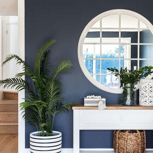シドニーの中サイズのビーチスタイルのおしゃれな独立型ファミリールーム (青い壁、無垢フローリング、据え置き型テレビ) の写真
