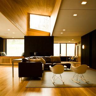 Aménagement d'une grand salle de séjour moderne ouverte avec un mur noir, un sol en bois clair, aucune cheminée et aucun téléviseur.
