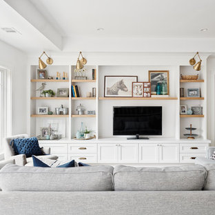 Example of a large beach style open concept light wood floor and brown floor family room design in San Francisco with white walls, no fireplace and a media wall