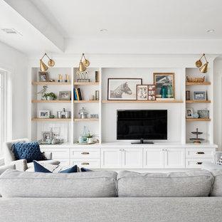 Modelo de sala de estar abierta, marinera, grande, sin chimenea, con paredes blancas, pared multimedia, suelo de madera clara y suelo marrón