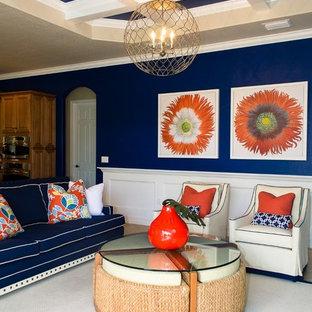 マイアミの中サイズのトロピカルスタイルのおしゃれなファミリールーム (青い壁、磁器タイルの床、壁掛け型テレビ、ベージュの床) の写真
