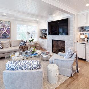 Стильный дизайн: открытая гостиная комната в стиле современная классика с домашним баром, белыми стенами, светлым паркетным полом, стандартным камином, фасадом камина из камня и отдельно стоящим ТВ - последний тренд