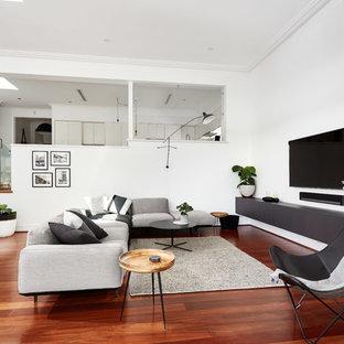 Diseño de sala de estar actual, de tamaño medio, sin chimenea, con paredes blancas, suelo de madera en tonos medios, televisor colgado en la pared y suelo rojo