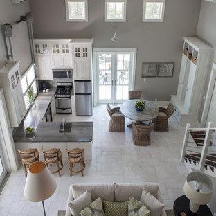 Foto de sala de estar abierta, costera, grande, con paredes grises, suelo de travertino y televisor colgado en la pared