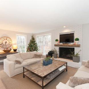 Ejemplo de sala de estar cerrada, campestre, de tamaño medio, con chimenea tradicional, marco de chimenea de ladrillo, paredes grises, suelo de madera en tonos medios y televisor colgado en la pared