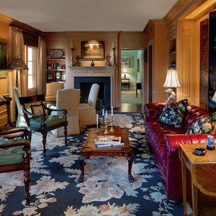 Cette photo montre une salle de séjour chic avec un sol en bois brun, une cheminée standard, un manteau de cheminée en plâtre et un mur orange.