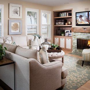 サンディエゴの中サイズのビーチスタイルのおしゃれなファミリールーム (タイルの暖炉まわり、ベージュの壁、淡色無垢フローリング、標準型暖炉、壁掛け型テレビ) の写真