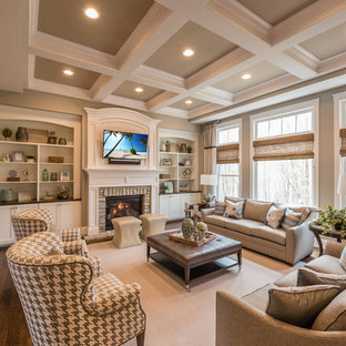 Family room - traditional enclosed dark wood floor family room idea in Cincinnati with beige walls, a standard fireplace, a stone fireplace and a wall-mounted tv