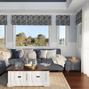 Inspiration for a large beach style open concept family room in Sunshine Coast with multi-coloured walls, dark hardwood floors, a wall-mounted tv, brown floor, coffered and decorative wall panelling.