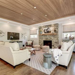 Modelo de sala de estar abierta, tradicional renovada, con paredes grises, chimenea tradicional, marco de chimenea de piedra y televisor colgado en la pared