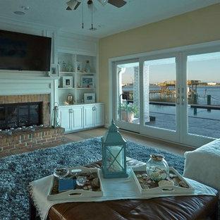 ジャクソンビルの広いビーチスタイルのおしゃれな独立型ファミリールーム (ベージュの壁、淡色無垢フローリング、標準型暖炉、レンガの暖炉まわり、壁掛け型テレビ) の写真