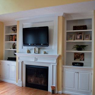 Idée de décoration pour une grande salle de séjour tradition avec un mur jaune, un sol en bois clair, une cheminée standard, un manteau de cheminée en bois et un téléviseur fixé au mur.