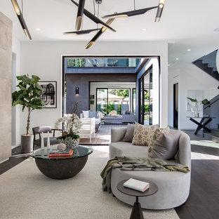 ロサンゼルスのコンテンポラリースタイルのおしゃれなファミリールーム (濃色無垢フローリング、横長型暖炉、コンクリートの暖炉まわり、茶色い床、白い壁) の写真