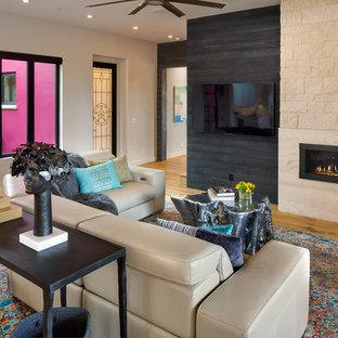Foto de sala de estar de estilo americano con paredes blancas, suelo de madera en tonos medios, chimenea lineal, marco de chimenea de piedra, televisor colgado en la pared y suelo marrón
