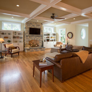 Inspiration for a large timeless open concept medium tone wood floor and brown floor family room remodel in Other with beige walls, a standard fireplace, a stone fireplace and a wall-mounted tv