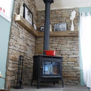 リッチモンドの中くらいのビーチスタイルのおしゃれなオープンリビング (青い壁、無垢フローリング、コーナー設置型暖炉、金属の暖炉まわり、据え置き型テレビ) の写真