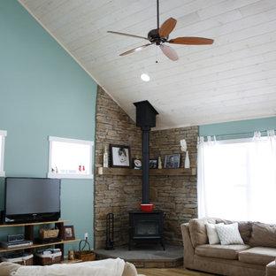リッチモンドの中サイズのビーチスタイルのおしゃれなファミリールーム (青い壁、無垢フローリング、金属の暖炉まわり、据え置き型テレビ、薪ストーブ) の写真