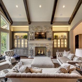 Ejemplo de sala de estar tradicional, grande, con paredes beige, suelo de madera oscura, chimenea tradicional, marco de chimenea de piedra y televisor colgado en la pared