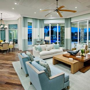 Foto di un grande soggiorno tropicale aperto con pareti blu, nessuna TV e pavimento in legno massello medio