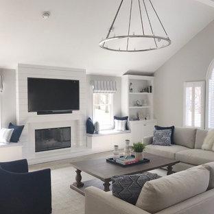 ニューヨークの大きいビーチスタイルのおしゃれな独立型ファミリールーム (グレーの壁、磁器タイルの床、標準型暖炉、木材の暖炉まわり、埋込式メディアウォール、グレーの床) の写真