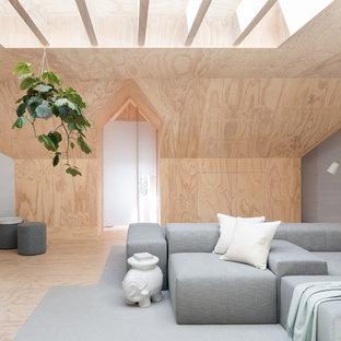 Стильный дизайн: открытая гостиная комната в скандинавском стиле с полом из фанеры и бежевыми стенами без камина - последний тренд