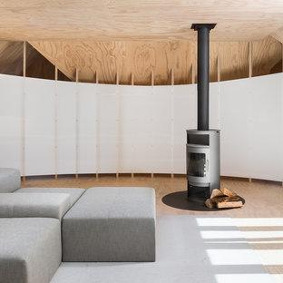 Immagine di un soggiorno scandinavo stile loft con pavimento in compensato e stufa a legna
