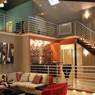 Ispirazione per un ampio soggiorno design stile loft con pareti arancioni, pavimento in bambù e TV a parete