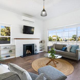 他の地域のコンテンポラリースタイルのおしゃれなオープンリビング (ライブラリー、白い壁、ラミネートの床、レンガの暖炉まわり、壁掛け型テレビ、茶色い床) の写真