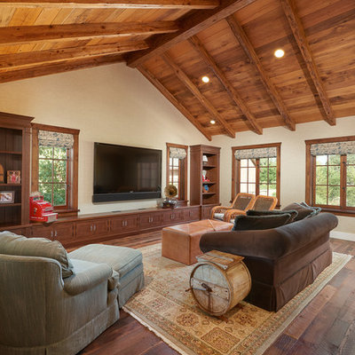 Family room - large rustic open concept dark wood floor family room idea in Santa Barbara with beige walls, no fireplace and a wall-mounted tv