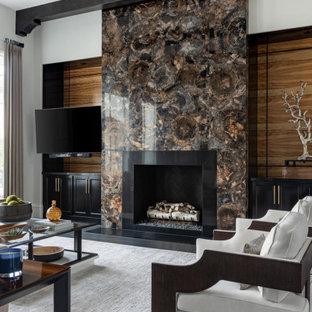 Idée de décoration pour une grande salle de séjour méditerranéenne ouverte avec un mur multicolore, un sol en bois foncé, une cheminée standard, un manteau de cheminée en pierre, un téléviseur fixé au mur et un sol noir.