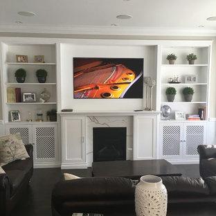 Foto de sala de estar abierta, tradicional renovada, pequeña, con paredes grises, suelo de madera oscura, chimenea tradicional, marco de chimenea de madera, pared multimedia y suelo marrón