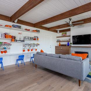 Modelo de sala de estar abierta, vintage, de tamaño medio, con paredes blancas, suelo de madera clara, chimenea tradicional, marco de chimenea de hormigón y televisor colgado en la pared