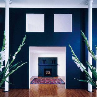ニューヨークの小さいおしゃれなファミリールーム (ライブラリー、青い壁、濃色無垢フローリング、コーナー設置型暖炉、漆喰の暖炉まわり、内蔵型テレビ、茶色い床) の写真