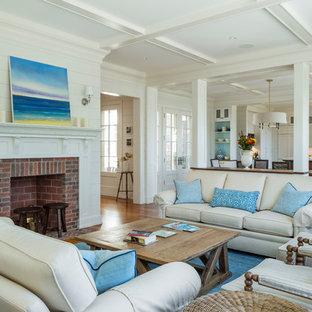 プロビデンスの中くらいのビーチスタイルのおしゃれなオープンリビング (白い壁、無垢フローリング、標準型暖炉、レンガの暖炉まわり) の写真