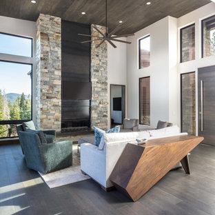 Неиссякаемый источник вдохновения для домашнего уюта: большая открытая гостиная комната в стиле современная классика с белыми стенами, стандартным камином, фасадом камина из камня, телевизором на стене, деревянным потолком, темным паркетным полом и черным полом