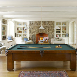 Mid-sized elegant enclosed light wood floor and brown floor game room photo in Boston with a standard fireplace, a stone fireplace, white walls and a concealed tv
