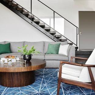 Modelo de sala de estar cerrada, vintage, grande, sin televisor, con paredes blancas, suelo de madera clara, chimenea lineal, marco de chimenea de baldosas y/o azulejos y suelo beige