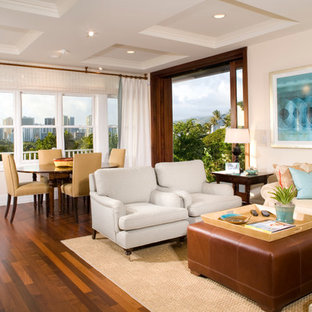 This is an example of a mid-sized tropical open concept family room in Hawaii with beige walls, dark hardwood floors, no fireplace and no tv.