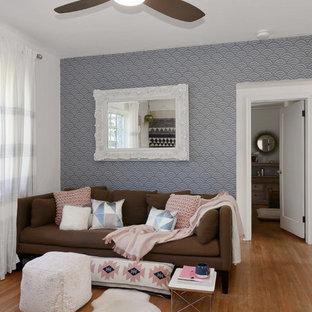 Diseño de sala de estar abierta, ecléctica, pequeña, sin chimenea, con paredes rosas, suelo de madera clara, televisor colgado en la pared y suelo marrón