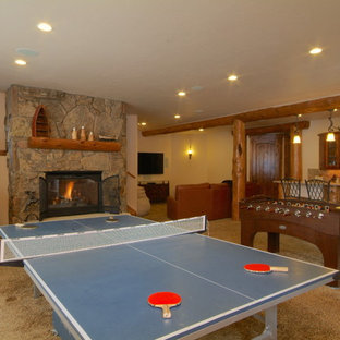 Mountain style enclosed carpeted and beige floor game room photo in Denver with beige walls, a standard fireplace, a stone fireplace and a wall-mounted tv
