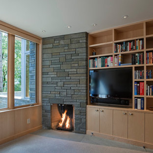 Trendy enclosed carpeted family room library photo in Seattle with a standard fireplace, a stone fireplace and a media wall