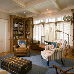 Example of a beach style enclosed family room library design in Charleston with beige walls